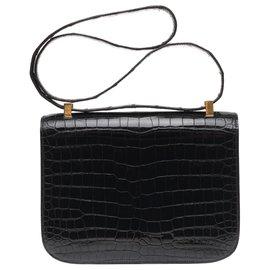 Hermès-Exceptionnel Hermès Constance 23 en Crocodile porosus noir, garniture en métal plaqué or-Noir